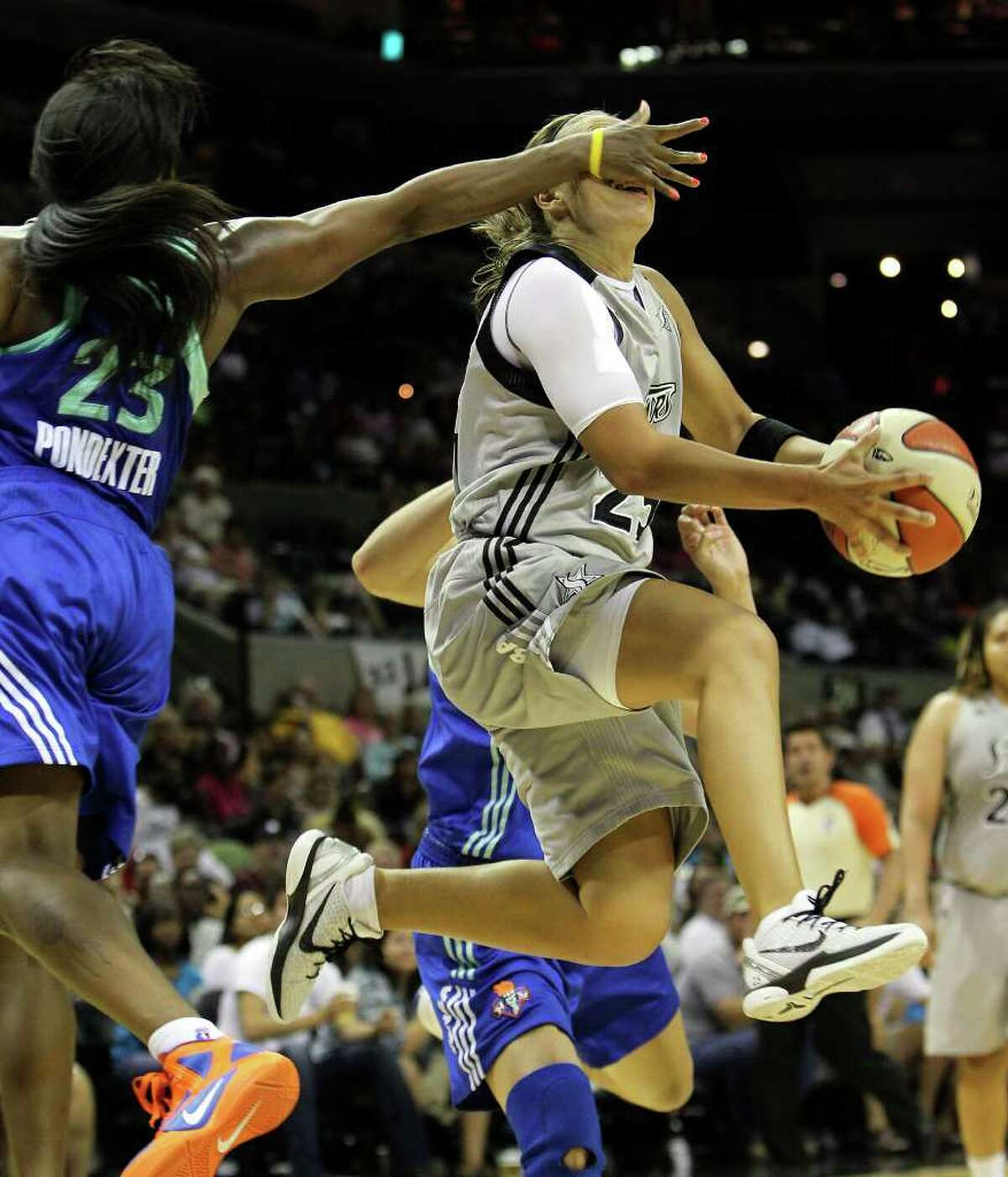 Silver Stars' Becky Hammon (right) gets a hand to the face while driving to the basket by New York Liberty's Cappie Pondexter (23) in the second half at the AT&T Center on Friday, July 8, 2011. Silver Stars lose to Liberty, 73-76. Kin Man Hui/kmhui@express-news.net