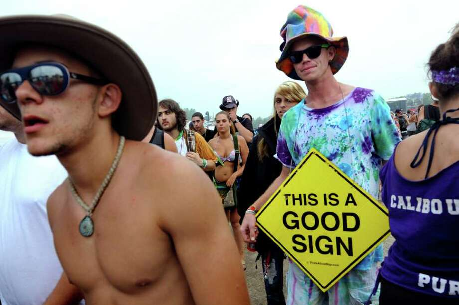 Brandon Swift, 23, of Key West, Fla., right, carries a message at Camp Bisco on Friday, July 8, 2011, in Pattersonville, N.Y. (Cindy Schultz / Times Union) Photo: Cindy Schultz