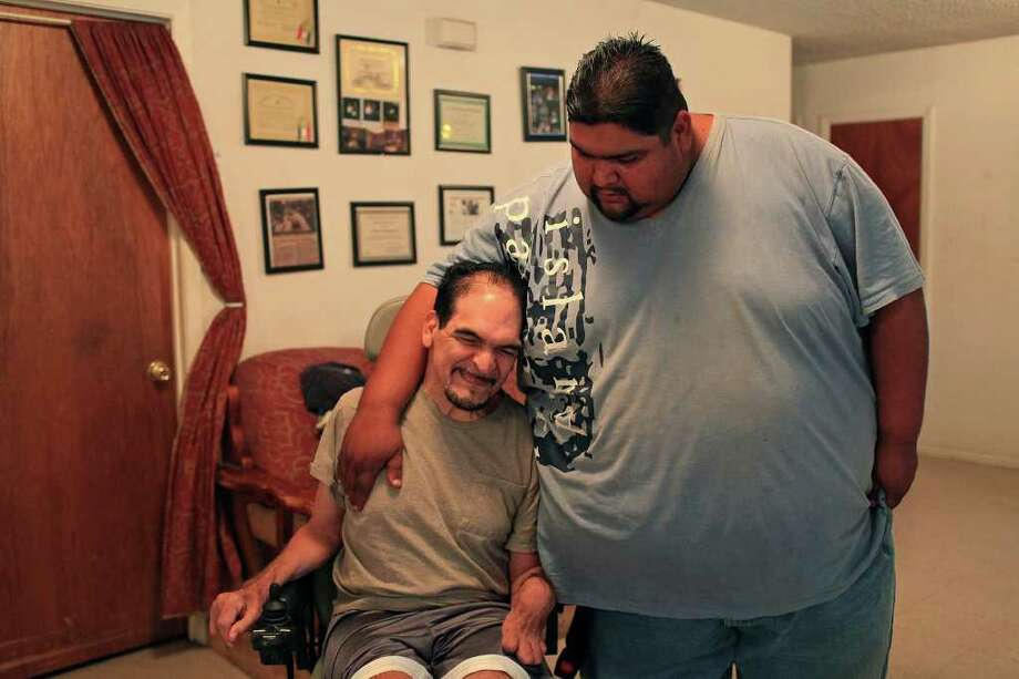 "Jorge Constantino, right, hugs his father, Ignacio ""Butch"" Constantino at their home on Thursday, July 7, 2011. ""They're my inspiration,"" Jorge said of his parents who have cerebral palsy and his father suffered a stroke. Photo: LISA KRANTZ, LISA KRANTZ/lkrantz@express-news.net / SAN ANTONIO EXPRESS-NEWS"