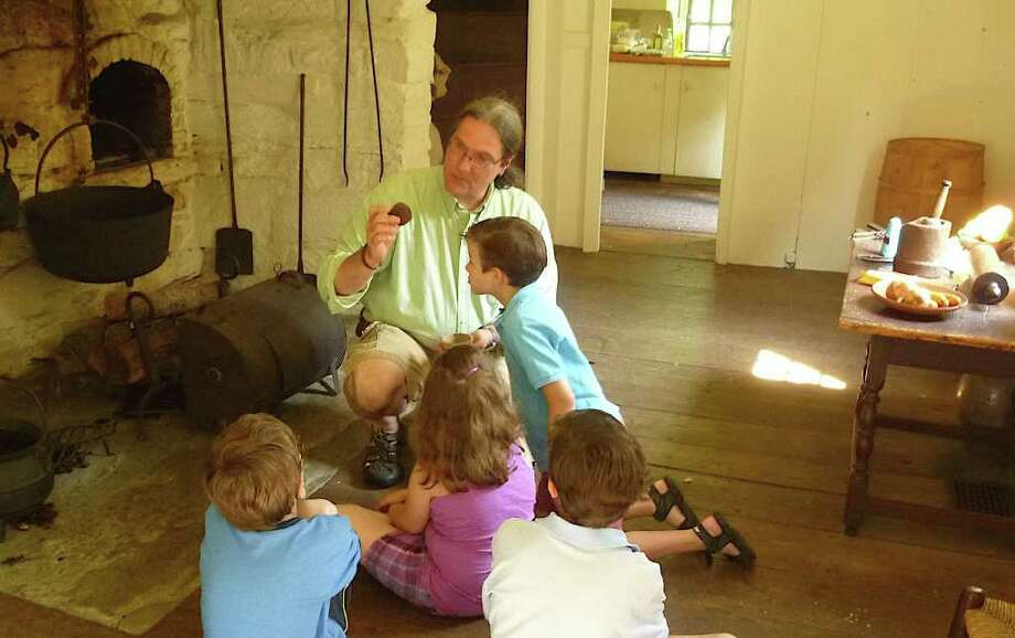 History Camp leader Walt Matis shows young campers at the historic Ogden House a pomander ball, which was used as a fragrance to mask  odors in Colonial homes. Photo: Contributed Photo/Mike Lauterbor, Contributed Photo / Fairfield Citizen contributed