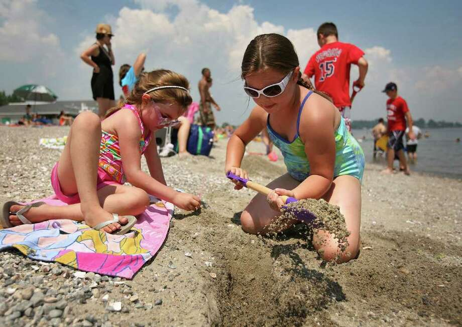 Cousins Lena Fulton-Wright, 6, left of Harrisburg, VA, and Erika Eggers, 7 of Trumbull, wear sunglasses during a day at Penfield Beach in Fairfield on Wednesday, July 6, 2011. Photo: Brian A. Pounds / Connecticut Post