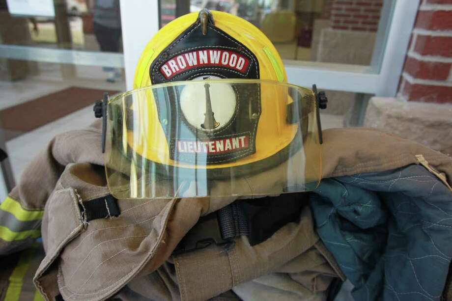 Members of the Brownwood Fire Department placed the bunker gear of Shannon Stone on a table during a benefit barbecue in his honor at the Brownwood Sherriff's and Police Department Office in Brownwood, Texas, Friday, July 8, 2011.  Stone died after complication from falling over a guardrail at a Texas Rangers baseballl game Thursday, July 7. (AP Photo/ Jeffery Washington) Photo: Jeffery Washington, FRE / Copyright: Jeffery Washington Photography