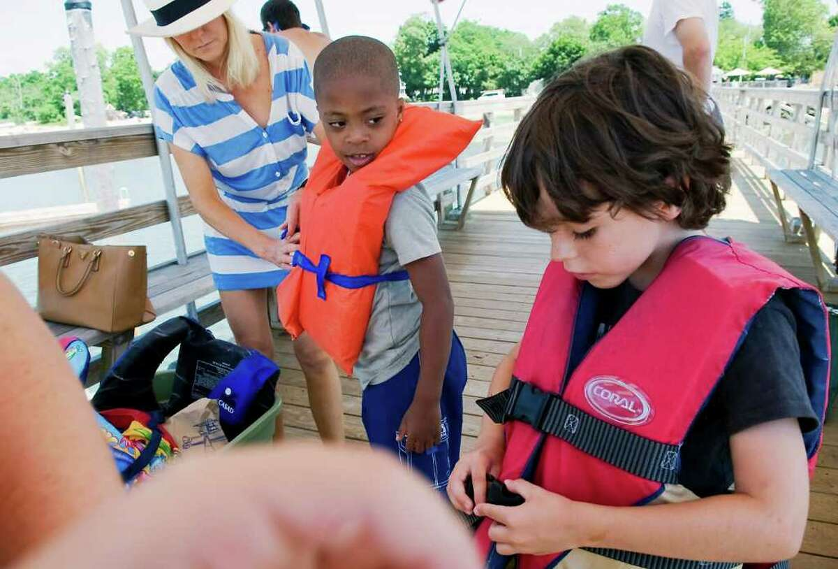 Dawn Konzerowsky helps Seven Smith, 7, and her son Max Konzerwosky, 7, with their life jackets as they spend the day at the beach in Darien, Conn. on Saturday July 9, 2011. Seven will be staying with the Konzerowsky family for two weeks as part of the Fresh Air Fund.