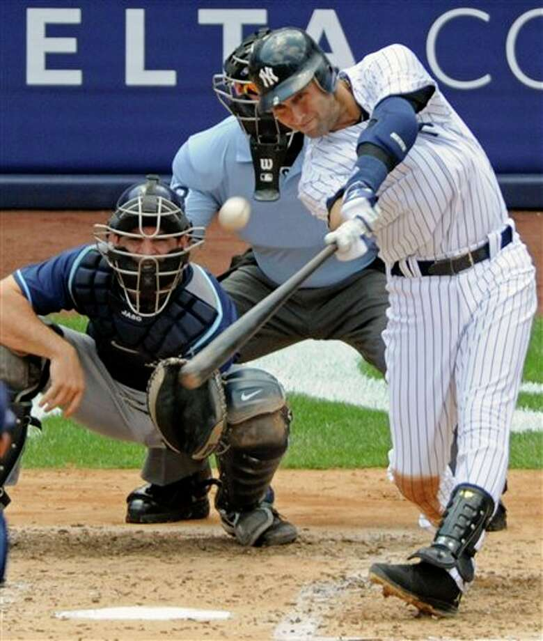 New York Yankees' Derek Jeter hits a home run for his 3,000th career hit during the third inning of a baseball game against the Tampa Bay Rays, Saturday, July 9, 2011, at Yankee Stadium in New York. Rays catcher John Jaso, pitcher David Price, left, and umpire Jim Wolf look on. Jeter became the 28th major leaguer to hit the milestone and also the first Yankees player. (AP Photo/Bill Kostroun) Photo: Bill Kostroun, Associated Press / FR51951 AP