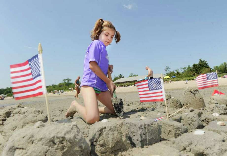Emery Bahna, 7, of Darien, constructs her sand castle with tiny American flags during the Greenwich Arts Council's Sand Blast!, sand sculpture festival, at Greenwich Point Saturday, July 9, 2011. Photo: Bob Luckey / Greenwich Time