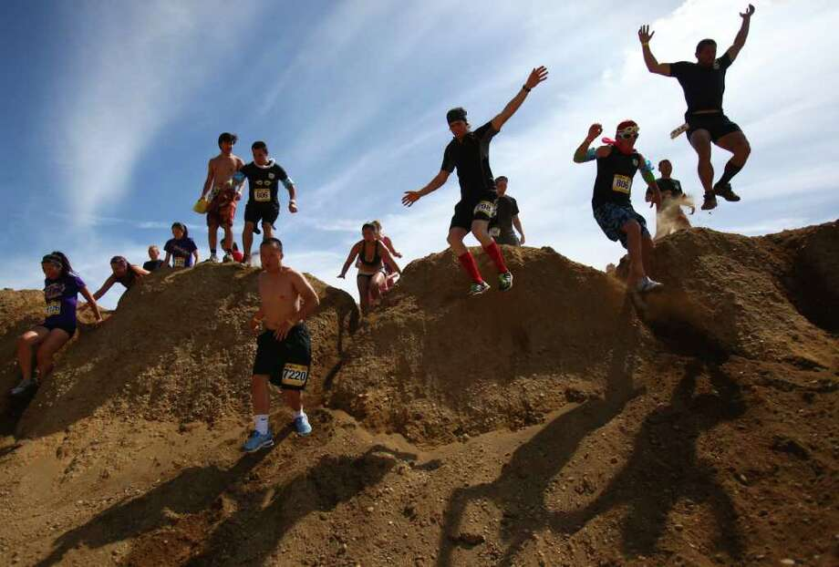 Some of the thousands of runner leap from a dirt hill during the Dirty Dash Seattle 10k mud run on Saturday, July 9, 2011 at PGP Motorsports Park in Kent. Nearly 4,000 people participated in the inaugural event in the Seattle area. Photo: JOSHUA TRUJILLO / SEATTLEPI.COM