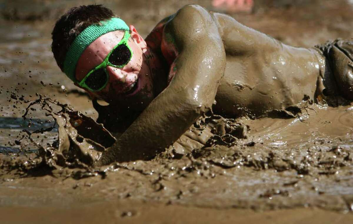 A participant slops through a mud pit during the Dirty Dash Seattle 10k mud run on Saturday, July 9, 2011 at PGP Motorsports Park in Kent.