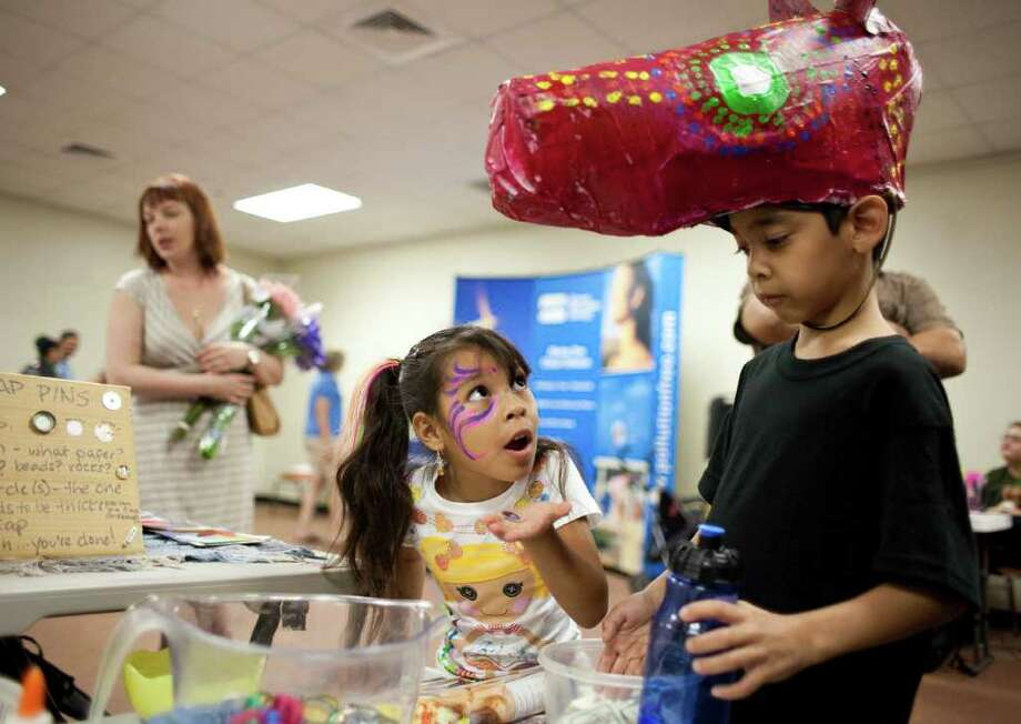 Gya Llanas, 5, left, of Houston, asks for another bottle cap as she Constantino Martinez, 8, of Houston, and other kids are encouraged to make bottle caps button pins during the Green Art Fest Saturday, July 9, 2011,  in Houston. The festival is the culmination event of the Floe Y Canto sustainable green theatre camp. ( Nick de la Torre / Houston Chronicle ) Photo: Nick De La Torre, Staff / © 2010 Houston Chronicle