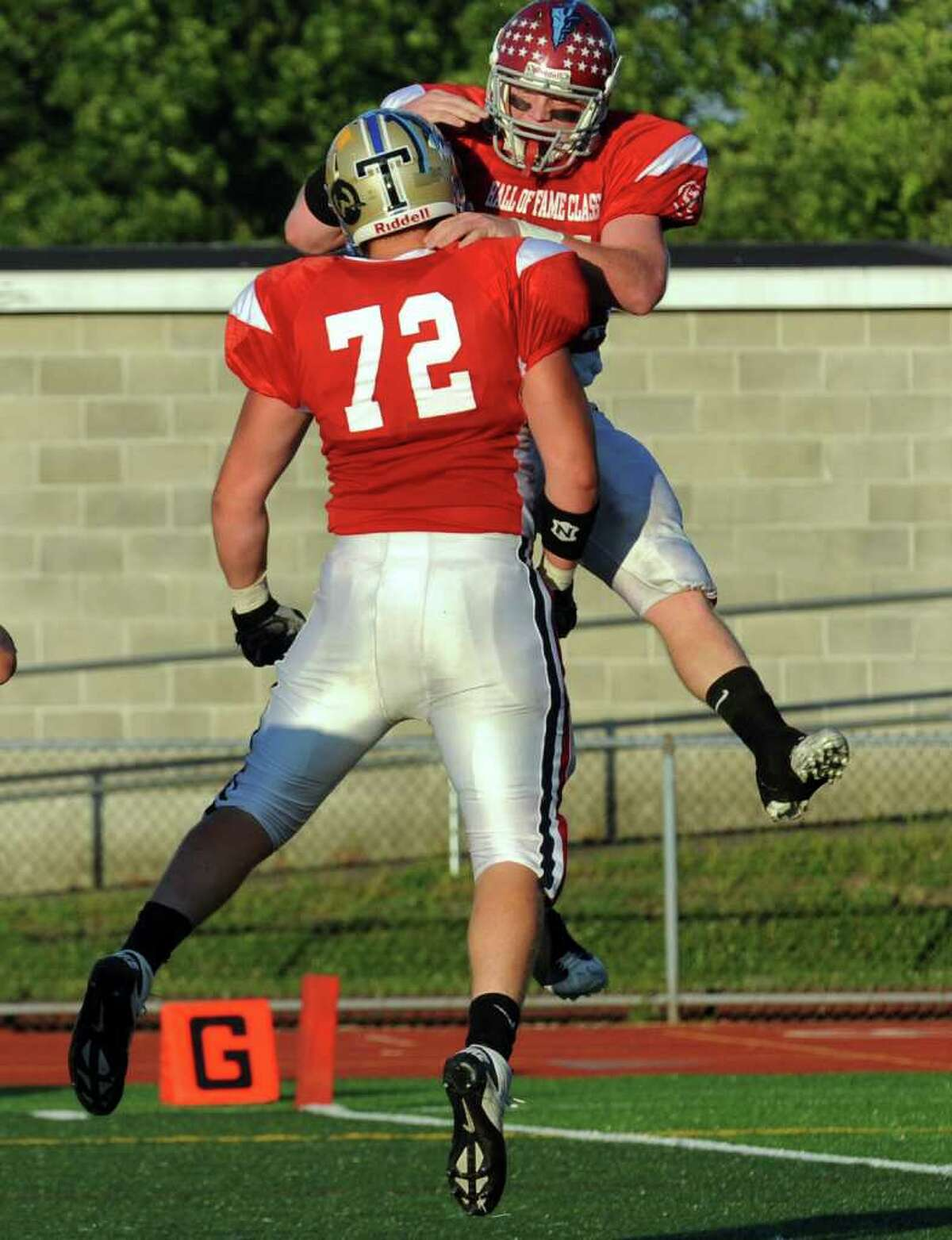 St. Joseph's #44 Tyler Matakevich, right, leaps in the air to celebrate his touchdown with teammate #72 Matt Datin, during Fairfield County vs. New Haven County All-star football action in West Haven, Conn. on Saturday July 9, 2011.