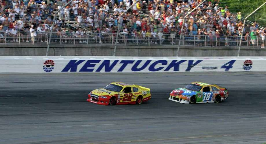 Kurt Busch (22) leads Kyle Busch (18) through the fourth turn early in the running of the inaugural NASCAR Sprint Cup Series auto race at the Kentucky Speedway, Saturday, July 9, 2011, in Sparta, Ky. (AP Photo/Garry Jones) Photo: Garry Jones, FRE / FR50389 AP