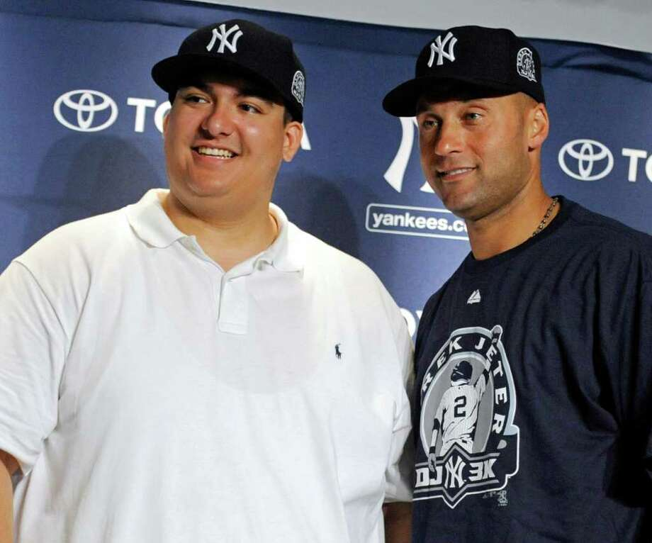 New York Yankees' Derek Jeter, right, poses with Christian Lopez  at a news conference after Lopez caught the 3,000 hit by Jeter during the third inning of a baseball game against the Tampa Bay Rays Saturday, July 9, 2011 at Yankee Stadium in New York. Lopez gave the ball to Jeter. (AP Photo/Bill Kostroun) Photo: Bill Kostroun