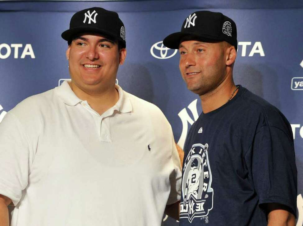 New York Yankees' Derek Jeter, right, with Christian Lopez, who caught Jeter's 3,000th career hit ball, are photographed during a news conference after a baseball game against the Tampa Bay Rays, Saturday, July 9, 2011, at Yankee Stadium in New York. The Yankees won 5-4. (AP Photo/Kathy Kmonicek)