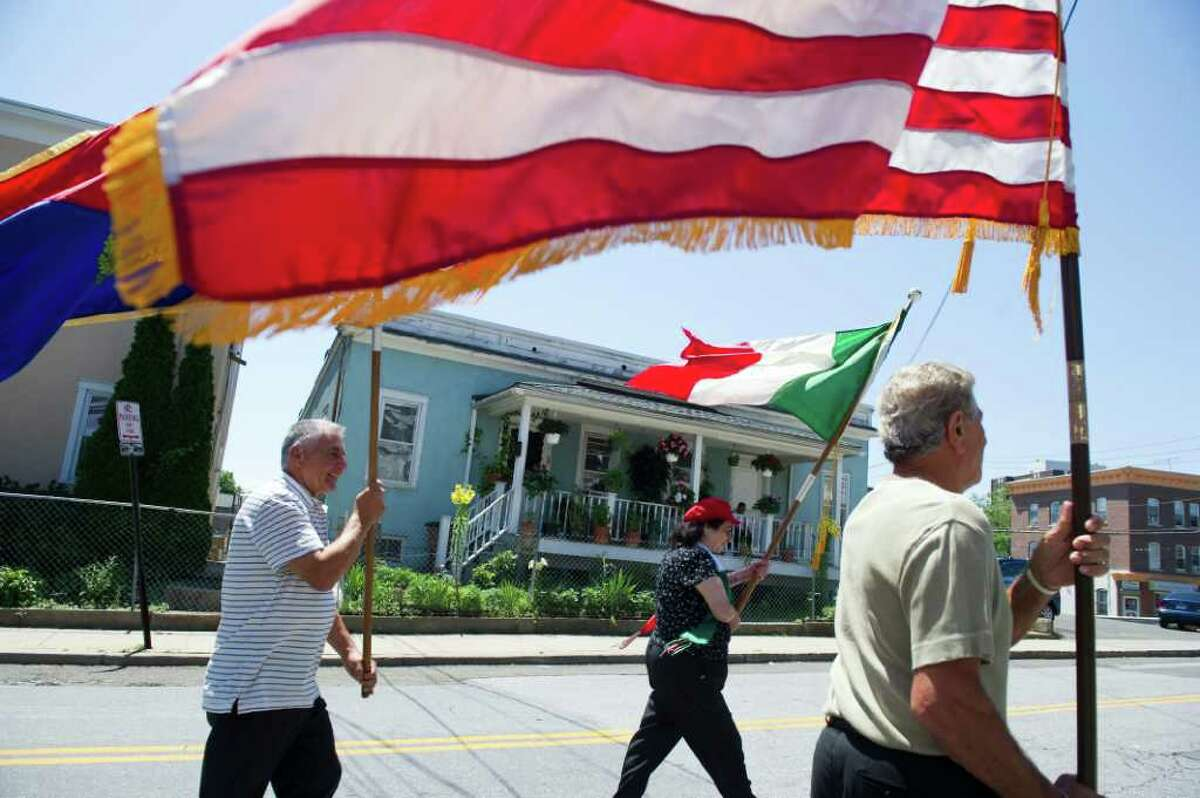 Thomas Pensiero, left, Theresa Mallozzi and Vinny Mallozzi lead the march as the Minturnese Social Club and Sacred Hearst Church hold the annual Festa de la Regna, or Festival of Wheat, celebrating harvest day with a parade on Schuyler Avenue July 10, 2011.