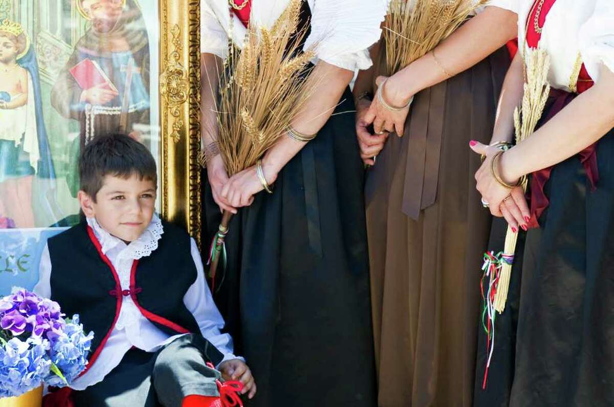 Francesco Franchina, 7, breaks from marching as the Minturnese Social Club and Sacred Hearst Church hold the annual Festa de la Regna, or Festival of Wheat, celebrating harvest day with a parade on Schuyler Avenue July 10, 2011.