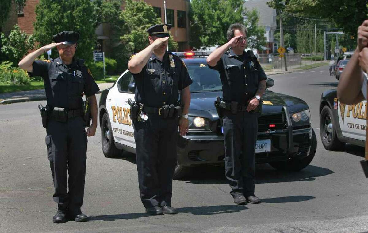 Bridgeport police officers, from left, Ken Ruge, Chuck Paris, and Paul Nikola, salute during the 18th annual Puerto Rican Day Parade in Bridgeport on Sunday, July 10, 2011.