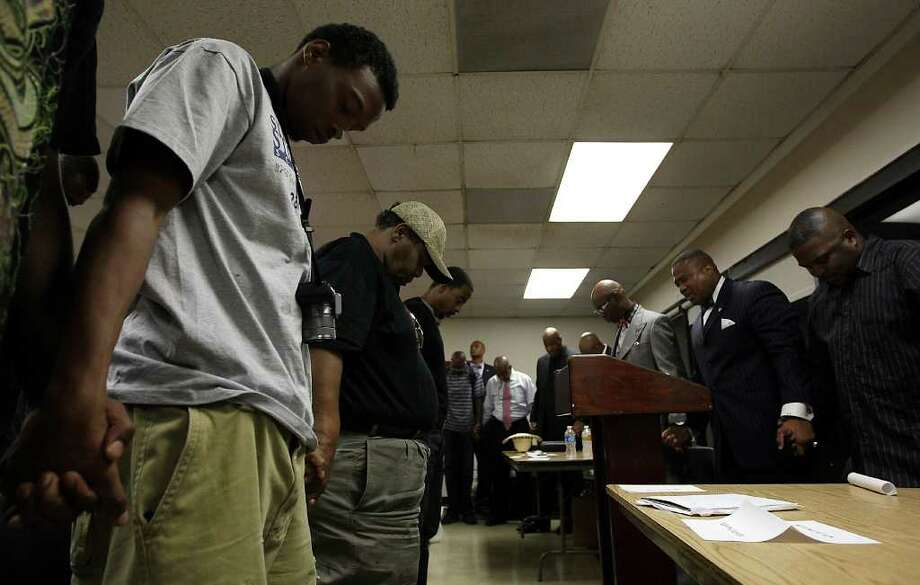 Everly James, 21, an ex-con prays with others at the end of a seminar hosted by Quanell X at Sunnyside Mutlipurpose Center,Wednesday, June 22, 2011, in Houston. The forum is for ex-cons who are struggling to find jobs. He said he was inspired by news recently that unemployment among blacks is at a 41-year high. The forum will feature 10 business owners who are all ex-cons. ( Karen Warren / Houston Chronicle ) Photo: Karen Warren, Staff / © 2011 Houston Chronicle