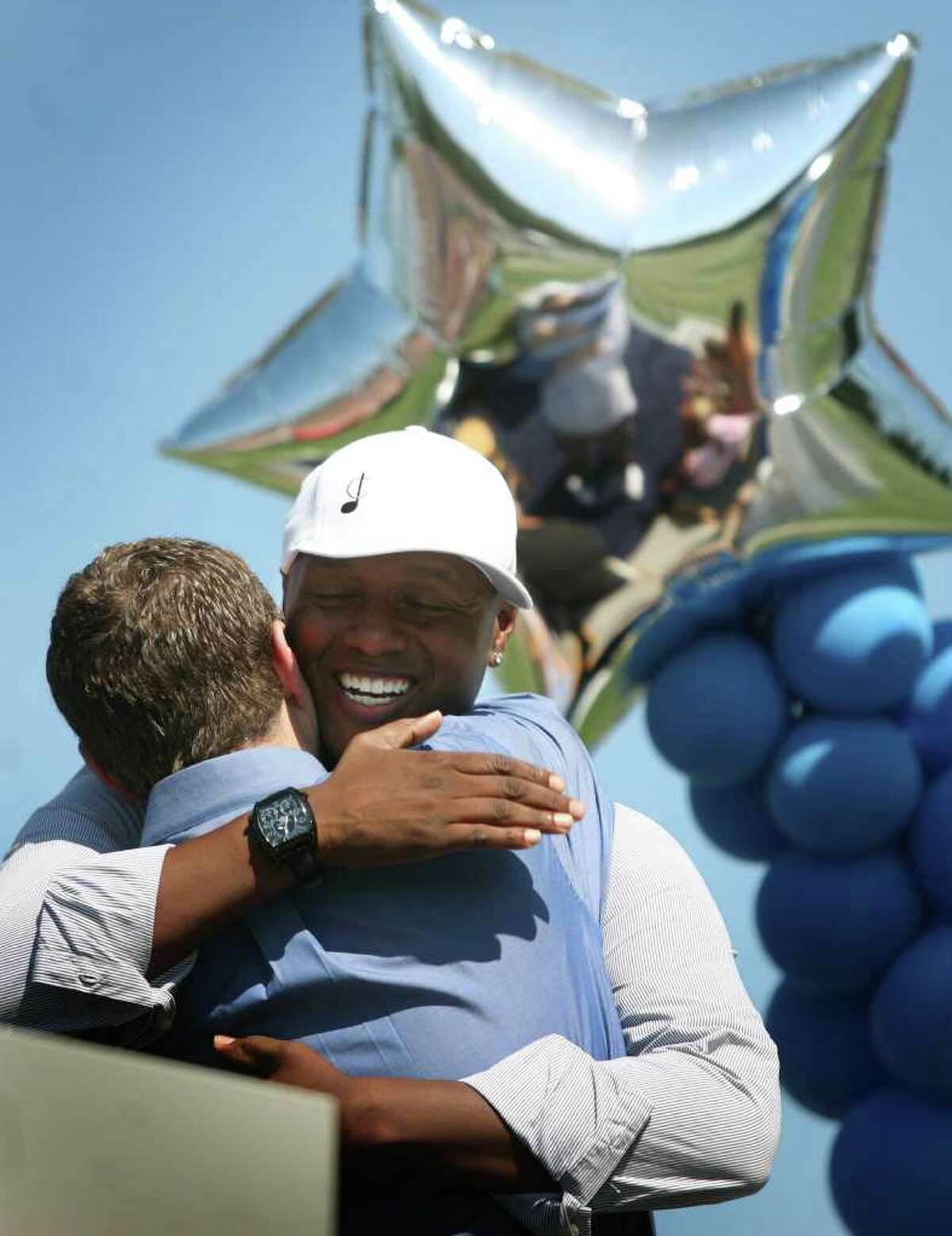 """Javier Colon, Stratford native and winner of the television singing competition """"The Voice"""", hugs his friend and event speaker Eric Nyquist during a welcome home celebration at Bunnell High School in Stratford on Sunday, July 10, 2011."""