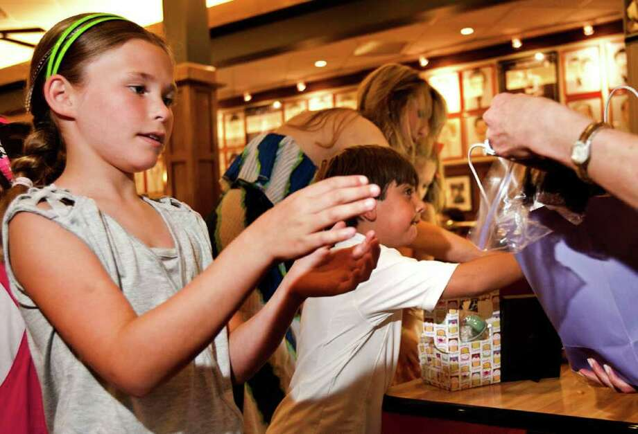 "Katie Korfin, 9 (front), buys some brownies from a volunteer, while Dylan Kessler, 6 (rear), rushes to put a donation in the collection jar during a bake sale fundraiser for the Berry family at Kenny and Ziggy's New York Delicatessen on Sunday afternoon, July 10, 2011 in Houston. Parents Robin and Joshua Berry were killed in a car accident over the July 4th weekend. The Berry's children, Peter, 9, Aaron, 8, and Willa, 6, were injured in the car accident in Fort Stockton, Texas. The fundraisers for the family on Sunday raised $13,000 at four locations in the Houston area, including $6,000 alone at Kenny and Ziggy's. ""The whole community is giving back to them because they gave so much to the community,"" said longtime friend Jean Kessler. The bake sale was organized by three close friends of the Berry family: Tamara Cohen, Blythe Grossman, and Tandy Harris. To donate to the family, please visit www.bethyeshurun.org and look for the donate button. There is a drop down scroll for the Perlo Berry fund. ( Patrick T. Fallon / Houston Chronicle ) Photo: Patrick T Fallon, Intern / © 2011 Houston Chronicle"