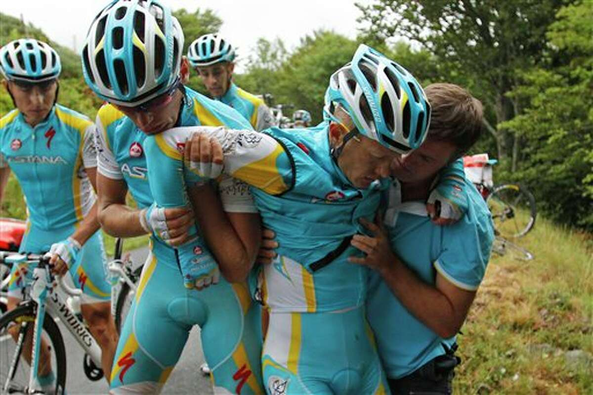 Alexande Vinokourov of Kazakhstan, second right, is helped by his teammates after crashing during the 9th stage of the Tour de France cycling race over 208 kilometers (129 miles) starting in Issoire and finishing in Saint Flour, central France, Sunday July 10, 2011. (AP Photo/Christophe Ena)