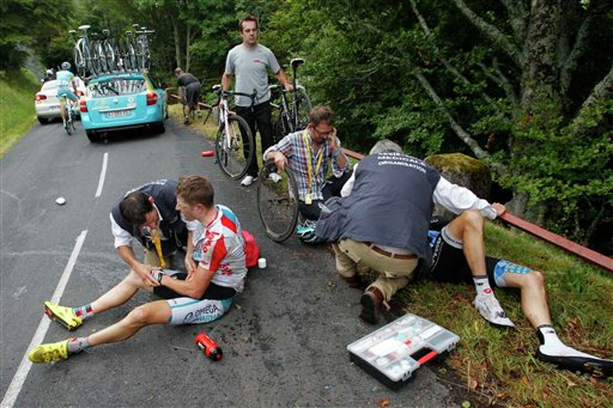 Frederik Willems of Belgium, left, and David Zabriskie of the US, right, are being treated by Tour de France doctors after crashing during the 9th stage of the Tour de France cycling race over 208 kilometers (129 miles) starting in Issoire and finishing in Saint Flour, central France, Sunday July 10, 2011. (AP Photo/Christophe Ena)