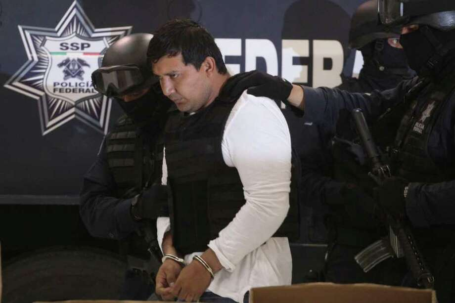 "Federal Police agents escort Jesus Enrique Aguilar, alias ""El Mamito"", to his presentation to the media in Mexico City, Monday July 4, 2011. Police believe Aguilar is connected with the killing of a U.S. Immigration and Customs Enforcement agent. According to authorities Aguilar is a former member of the Mexican Army and allegedly a co-founder of the Zetas drug cartel. (AP Photo/Alexandre Meneghini) Photo: Alexandre Meneghini, STF / AP"