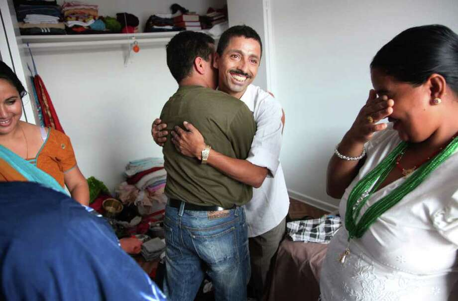 (center) Kushman Dhaurali, 30, embraces brother-in-law Puspa Kheral, just arrived from Nepal, as Kushma's sister Lachi Kheral weeps on July 5, 2011, in Houston.   The Bhutanese family lived together at a refugee camp in Nepal for almost 18 years.  ( Mayra Beltran / Chronicle ) Photo: Mayra Beltran, Staff / © 2011 Houston Chronicle