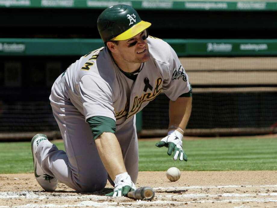 Oakland Athletics' Josh Willingham lifts himself off the ground after leaping to avoid an inside low pitch from Texas Rangers' Matt Harrison in the second inning of a baseball game Sunday, July 10, 2011, in Arlington, Texas. Willingham struck out in the at-bat.  (AP Photo/Tony Gutierrez) Photo: Tony Gutierrez, STF / AP