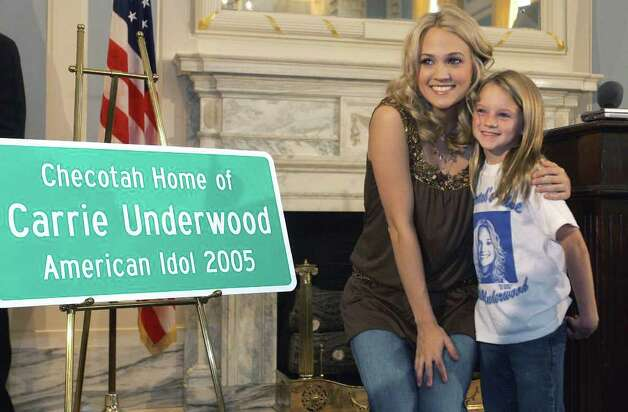 """American Idol"" Carrie Underwood, left, poses with Ashley Acker, 10, right, of South Lake, Texas, following a news conference at the state Capitol, in Oklahoma City, Wednesday, Aug. 10, 2005. Underwood was presented with a replica of a road sign to be placed in her hometown of Checotah, Okla. Photo: AP / AP"