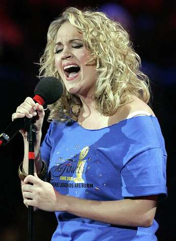 "** FILE ** American Idol winner Carrie Underwood sings the national anthem before the start of Game 4 of the NBA Finals in Auburn Hills, Mich., in a file photo from June 16, 2005. Underwood will sing classic jingles in a new television ad campaign for the Hershey Co. Underwood, a native of Checotah, will sing ""sometimes you feel like a nut ... sometimes you don't"" for Almond Joy and Mounds. Photo: JEFF ROBERSON, AP / AP"