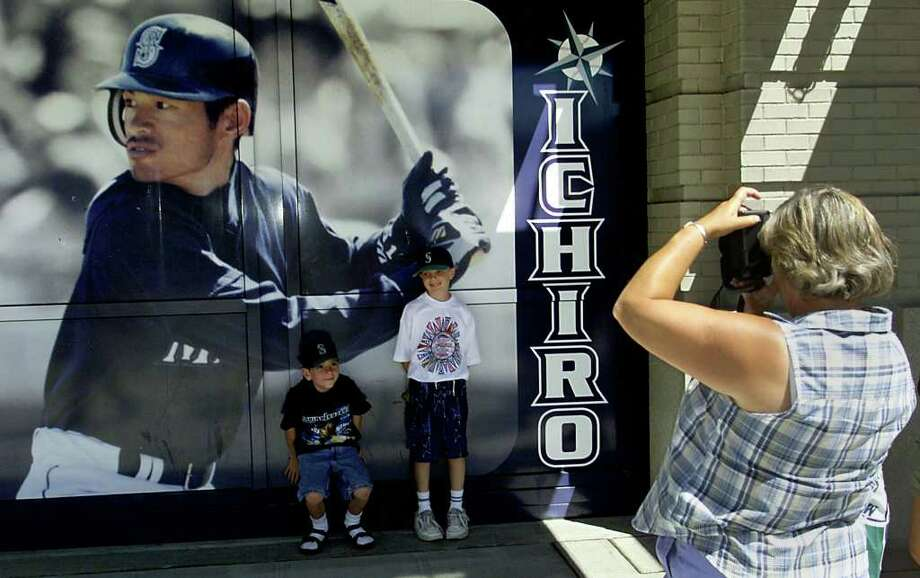 SEATTLE, UNITED STATES:  Ryan Jacobs (L) and Collins Sulgrove (R) stand for pictures in front of a mural of Seattle Mariners' Ichiro Suzuki of Japan for 2001 All-Star Game at Safeco Field 09 July 2001 in Seattle, Washington. Suzuki received 3.3 million votes to become the top vote getter in this years voting.  AFP PHOTO/Jeff HAYNES Photo: JEFF HAYNES, AFP/Getty Images / AFP