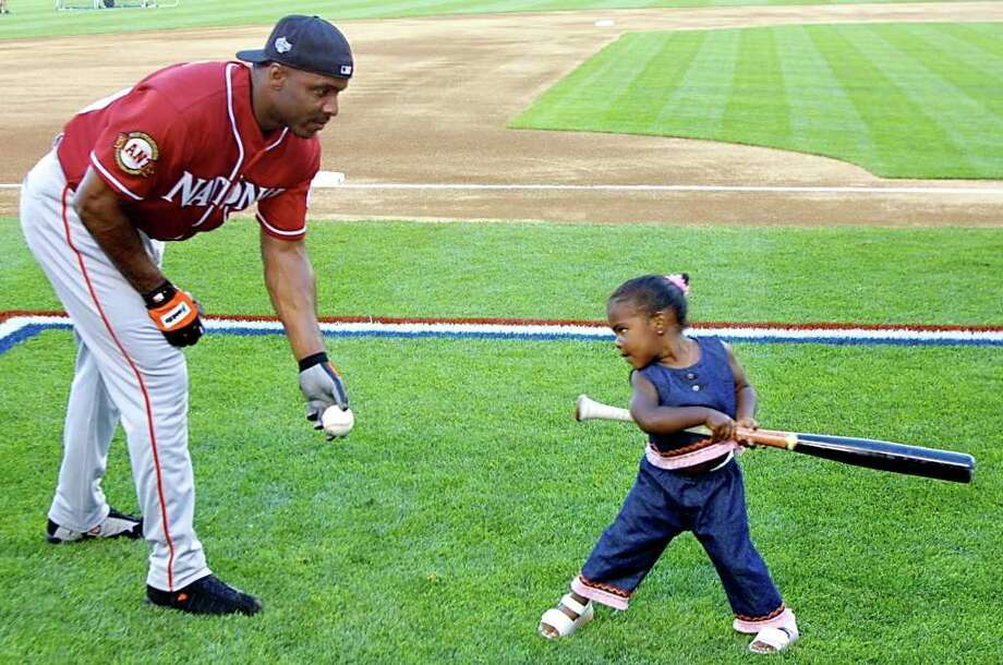 SEATTLE, UNITED STATES:  Barry Bonds (L) of the San Francisco Giants pitches to his daughter Aisha during the 2001 Home Run Derby 09 July, 2001, at Safeco Field in Seattle, Washington. The All-Star game will be 10 July, 2001.   AFP PHOTO/Dan LEVINE Photo: DAN LEVINE, AFP/Getty Images / AFP