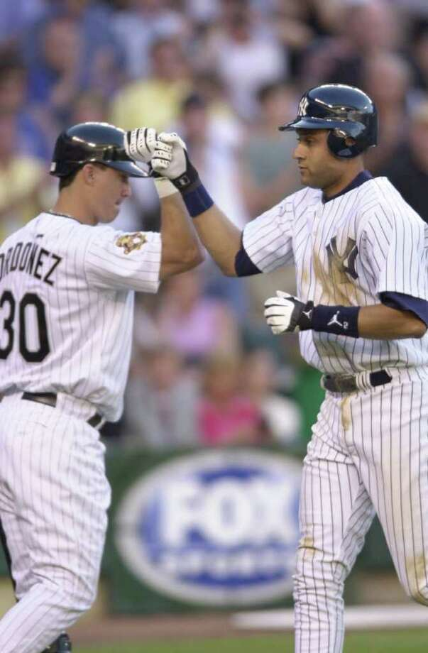 10 Jul 2001:  Derek Jeter (r) of the New York Yankees celebrates his home run with teammate Magglio Ordonez of the Chicago White Sox during the 2001 Major League Baseball All-Star Game at Safeco Field in  Seattle, Washington. DIGITAL IMAGE. Mandatory Credit: Otto Greule/Allsport Photo: Otto Greule Jr, Getty Images / Getty Images North America