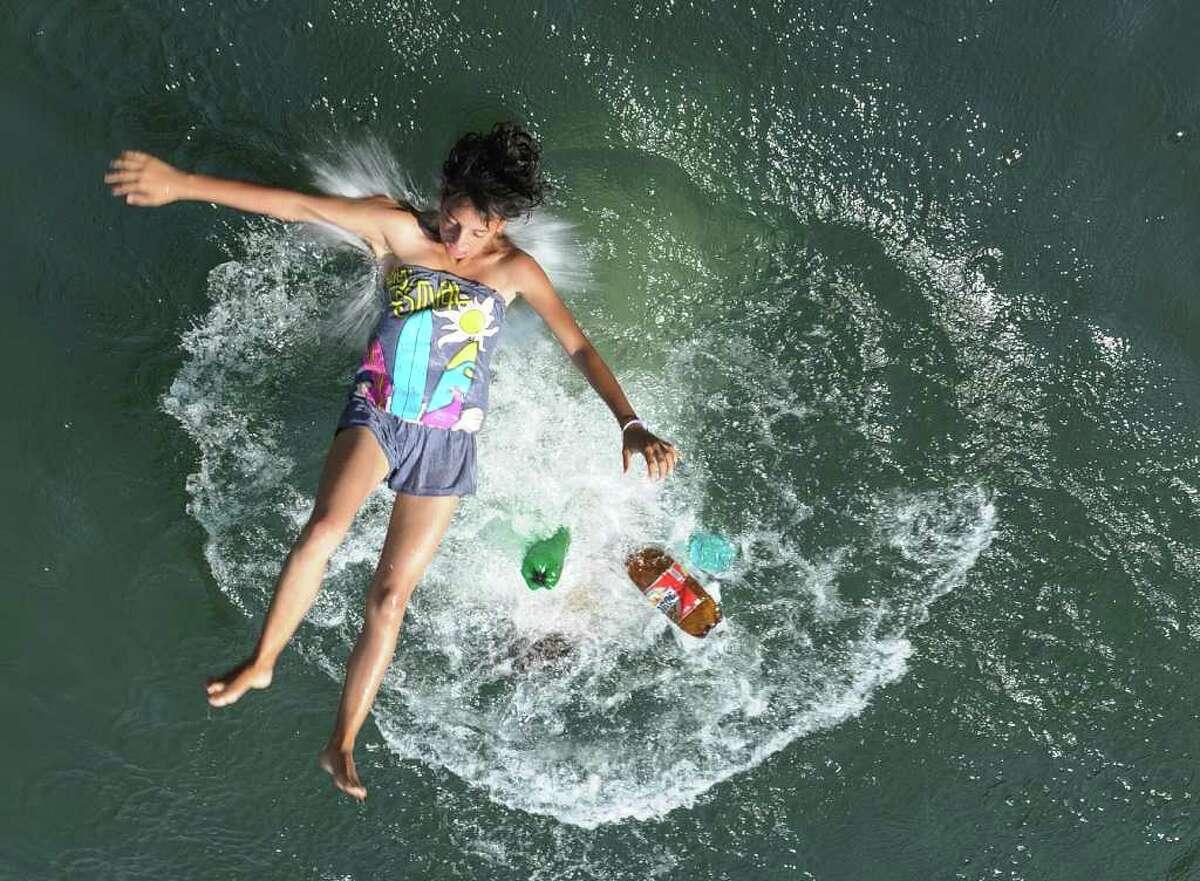 A Romanian girl jumps into the Dambovita river, in downtown Bucharest.