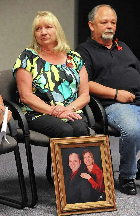 Cynthia Hebert displays a portrait of her children during the Hebert's  press conference on Monday. Younger sister Holly Hebert spoke about Bryan Hebert's life. Holly Hebert is also seen in the portrait. Guiseppe Barranco/The Enterprise Photo: Guiseppe Barranco
