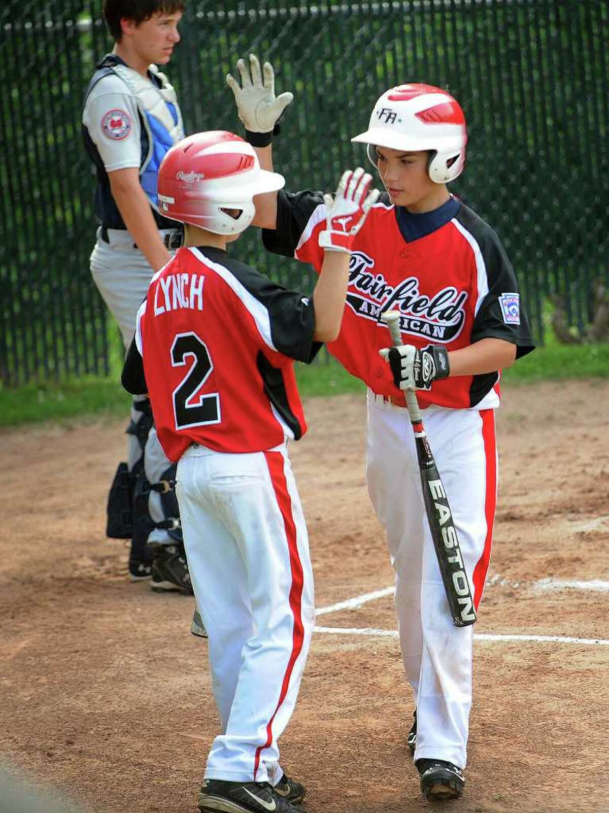 Fairfield American's Connor Lynch, left, greets teammate Sean Guiterrez at the plate after a first inning home run in their Little League matchup with Westport at Blackham School in Bridgeport on Monday, July 11, 2011.