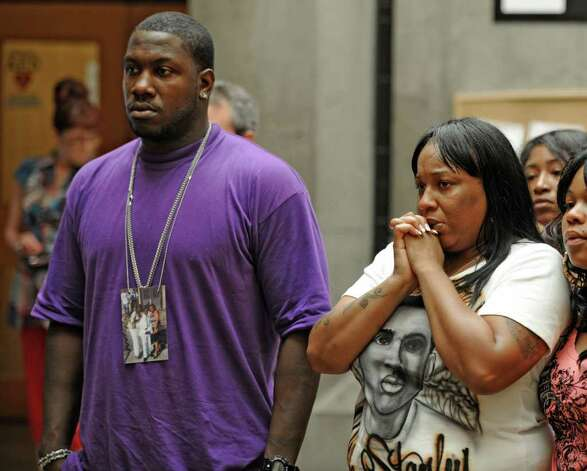 Eddie Stanley Sr., left and Tanisha Stanley, right listen to Schenectady, N.Y. Public Safety Commissioner as he makes the announcement at a press conference in Police Headquarters July 11, 2011, of the arrest of  James Wells of Brooklyn who is alleged to have been involved in the murder of their son basketball player Eddie Stanley. (Skip Dickstein / Times Union) Photo: SKIP DICKSTEIN / 00013870A