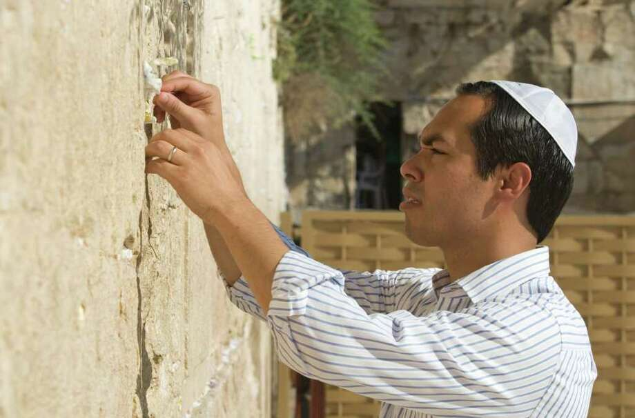San Antonio, Texas mayor Julian Castro inserts a note as he stands at Western Wall, the holiest site where Jews can pray, during his visit of Jerusalem's Old city, Monday, July 11, 2011. (AP Photos/Dan Balilty) Photo: Dan Balilty, Express-News / AP