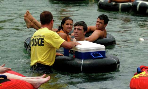 A New Braunfels, Texas police officer talks to tubers on the Comal river before opening their ice chest on Sunday July 2, 2006. Police there were wading into the water and searching ice chests for contraband such as glass containers, styrofoam cups or anything else illegal on the river. JOHN DAVENPORT / STAFF Photo: JOHN DAVENPORT, SAN ANTONIO EXPRESS-NEWS / SAN ANTONIO EXPRESS-NEWS