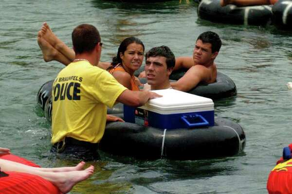 A New Braunfels, Texas police officer talks to tubers on the Comal river before opening their ice chest on Sunday July 2, 2006. Police there were wading into the water and searching ice chests for contraband such as glass containers, styrofoam cups or anything else illegal on the river. JOHN DAVENPORT / STAFF