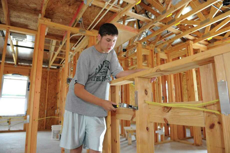 Patrick Massey (77065), a Troop 1177 scout member from St. Maximillan Kolbe Catholic Church, works on a Habitat for Humanity house located in Hamill Ranch community on 6/25/2011. Photo by Thomas Nguyen. Photo: Thomas Nguyen, Freelance / Freelance