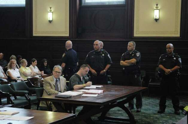Defense attorney Terence Kindlon, foreground left, and his client Michael Mosley sit at the defense table as law enforcement officers stand guard  in Judge Robert Jacon's courtroom at the Rensselaer County Courthouse on Tuesday morning, July 12, 2011, in Troy.  Michael Mosley was sentenced to life for the murders of Samuel Holley and Arica Lynn Schneider.  (Paul Buckowski / Times Union) Photo: Paul Buckowski / 00013874A