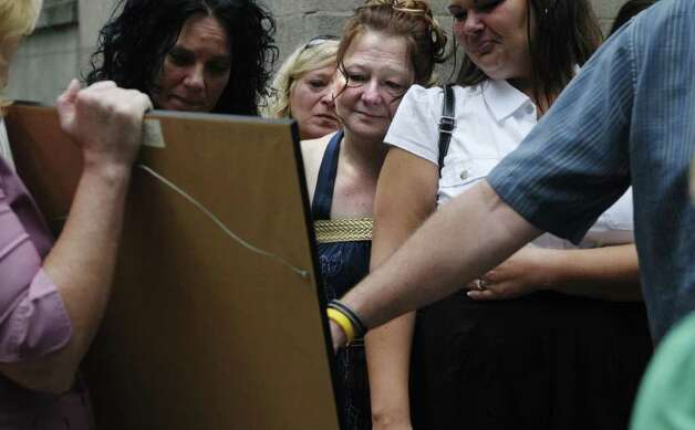 Robin Ritrovato, center, the mother of Arica Lynn Schneider, looks at an artist's drawing of her daughter  outside the Rensselaer County Courthouse on Tuesday morning, July 12, 2011, in Troy.  Michael Mosley was sentenced to life for the murders of Samuel Holley and Arica Lynn Schneider.  (Paul Buckowski / Times Union) Photo: Paul Buckowski / 00013874A