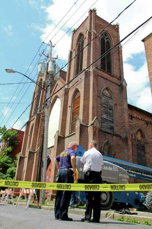 Battalion Chief Bill Hummel, of the Albany fire department, left, and Deputy Chief Joeseph Toomey, of the Albany fire department, stand outside of Trinity Church on Trinity Place, Albany which has suffered a series of recent structural collapses. Crews work to get the structure safely down on Tuesday, July 12, 2011. (Erin Colligan / Special To The Times Union)