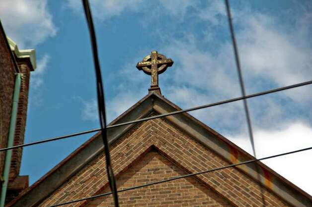 A cross on the top of Trinity Church on Trinity Place, Albany which has suffered a series of recent structural collapses. Crews work to get the structure safely down on Tuesday, July 12, 2011. (Erin Colligan / Special To The Times Union)