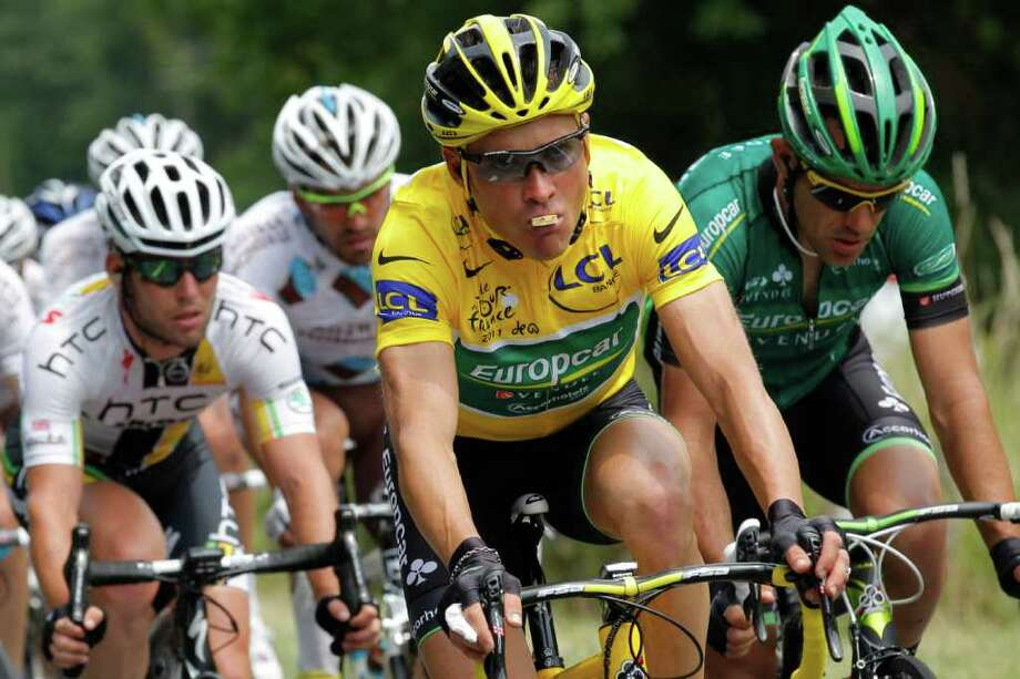 Thomas Voeckler of France, wearing the overall leader's yellow jersey, eats while riding in the pack with Mark Cavendish of Britain, left, during the 10th stage of the Tour de France cycling race over 158 kilometers (98.2 miles) starting in Aurillac and finishing in Carmaux, south central France, Tuesday July 12, 2011. (AP Photo/Christophe Ena) Photo: Christophe Ena, STF / AP