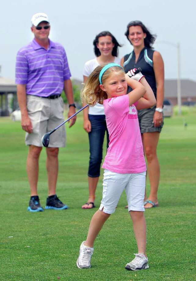 In this photo taken July 11, 2011, Reagan Kennedy, 6, takes a swing at The Links of Ireland Grove golf course in Bloomington, Ill., as her father, Steve; sister Cheyenne, 13; and mother Erin look on. Last week Reagan made a hole in one on the 85-yard third hole at the course. (AP Photo/The Pantagraph, David Proeber) Photo: David Proeber, MBR / The Pantagraph