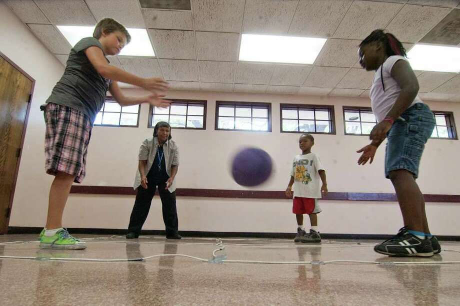 Gabrielle Patterson, 10; Rec Supervisor Deatra Edwards; Jaden Hughes, 6; and Kayla Norris, 7; play 4-square during take part in a Summer Enrichment Program at Platou Community Center.  Photo by R. Clayton McKee Photo: R. Clayton McKee, Freelance / © R. Clayton McKee