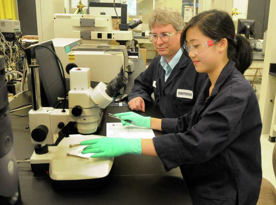 Education for Tomorrow Alliance intern Jaclyn Nguyen, a Caney Creek High School senior, looks at a slide in a microscope as her mentor, Doug Klewer. Senior Scientist at Huntsman Chemical, 8302 New Trails in The Woodlands, watches. EfTA works with companies too place  high school seniors as interns in their companies. Photo by David Hopper Photo: David Hopper, Freelance / freelance