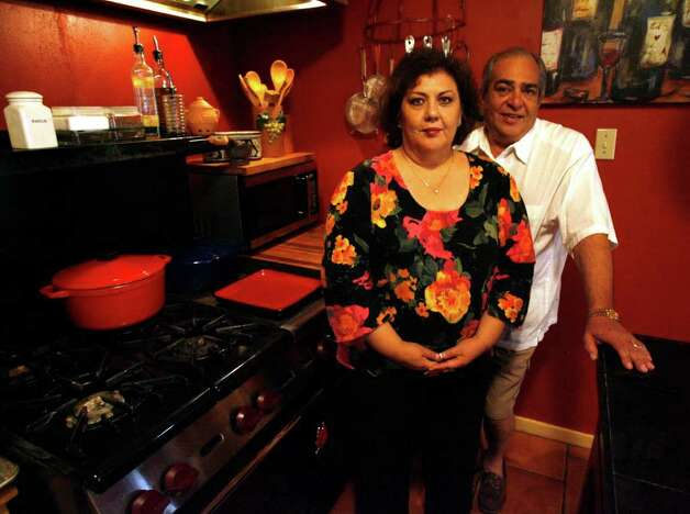 Roland and Genny Rodriguez's stand in front of their 36-inch Wolf range in the kitchen they renovated five years ago. Photo: OMAR PEREZ, San Antonio Express-News / SAN ANTONIO EXPRESS-NEWS