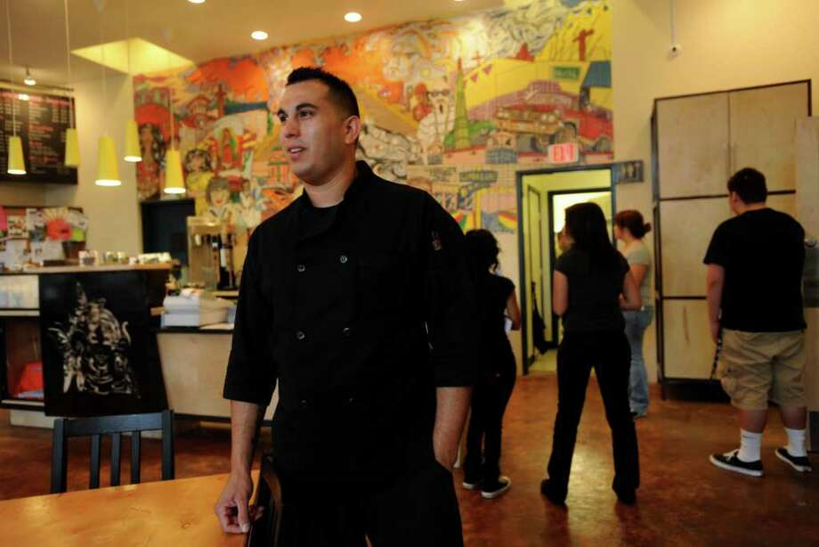 Edward Garcia, a chef at the Guadalupe Street Coffee, grew up in the nearby West Side neighborhood. He is elevating the cuisine offered at the coffee shop and teaching young volunteers about eating healthy and job skills. Photo: BILLY CALZADA, SAN ANTONIO EXPRESS-NEWS / gcalzada@express-news.net